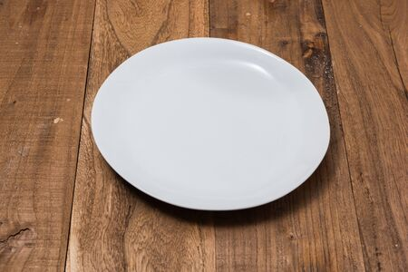 White Plate on brown wooden table background side view Stock fotó