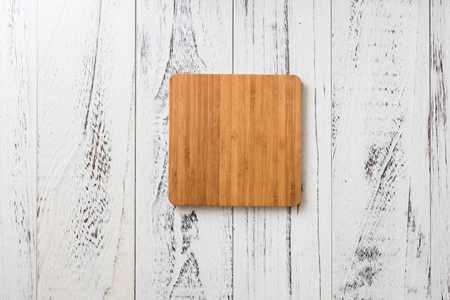 Square cutting board on white wooden table background