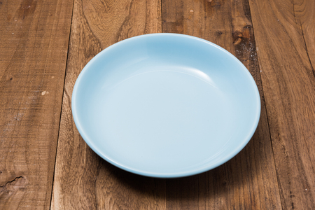 Blue Round Plate on brown wooden table background side view