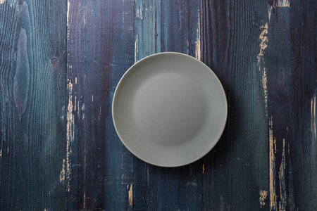 Green Round Plate on ocean blue wooden table background Stock fotó
