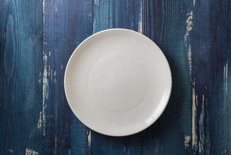 White Round Plate on ocean blue wooden table background