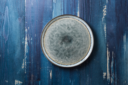 Round Plate on ocean blue wooden table background