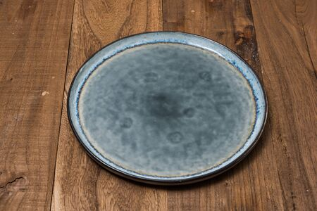 Round Plate on brown wooden table background side view Stock fotó