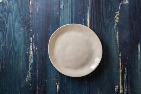 Beige Round Plate on ocean blue wooden table background Stock fotó