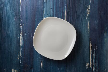 White Plate on ocean blue wooden table background