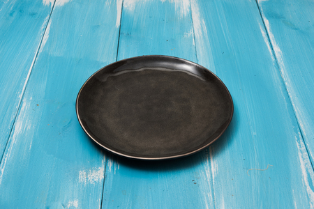 Round plate on blue wooden table with perspective side view