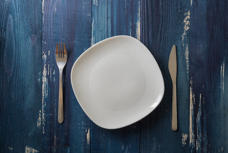 White Plate with utensils on ocean blue wooden table background Stock fotó