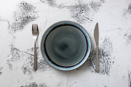 Round Plate with utensils on white scraped wooden table background Stock fotó