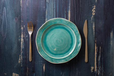 Turquoise Round Plate with utensils on ocean blue wooden table background