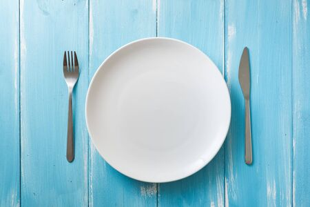 White Round Plate with utensils on blue wooden table background Stock fotó