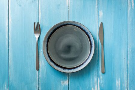 Round Plate with utensils on blue wooden table background