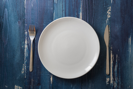White Round Plate with utensils on ocean blue wooden table background Stock fotó