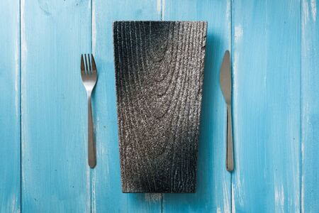 Japanese Plate with fork and knife on light blue wooden table background