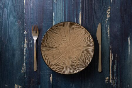 Round Plate with utensils on ocean blue wooden table background Stock fotó