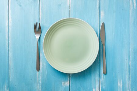 Green Round Plate with utensils on blue wooden table background Stock fotó