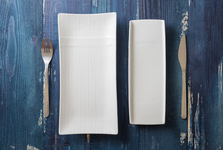 White rectangular Plates with fork and knife on ocean blue wooden table background