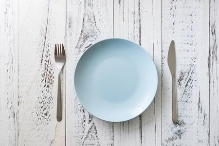 Blue Round Plate with utensils on white wooden table background
