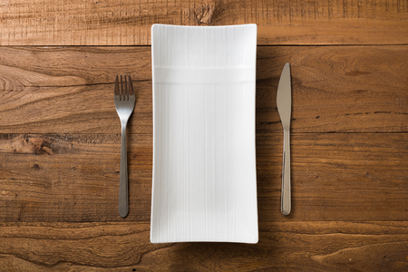 White rectangular Plate with fork and knife on brown wooden table background Stock fotó