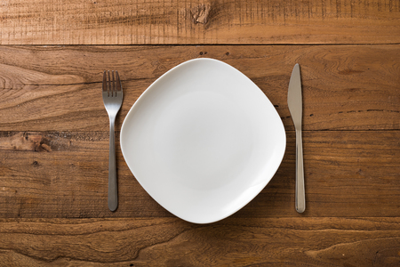 White Plate with utensils on brown wooden table background