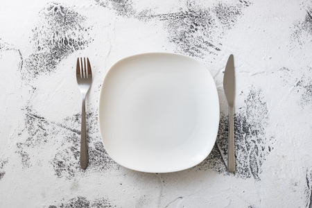 White Round Plate with utensils on white scraped wooden table background Stock fotó