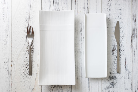 White rectangular Plates with fork and knife on white wooden table background
