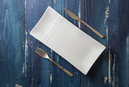 White rectangular Plate with fork and knife on ocean blue wooden table background