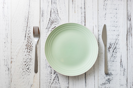 Green Round Plate with utensils on white wooden table background Stock fotó