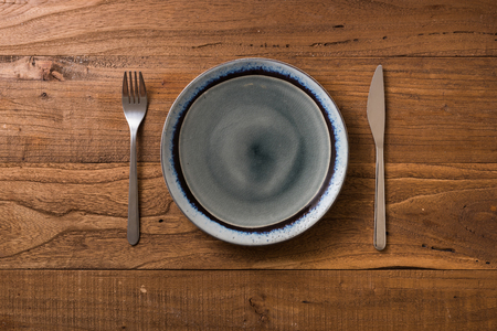 Round Plate with utensils on brown wooden table background Stock fotó
