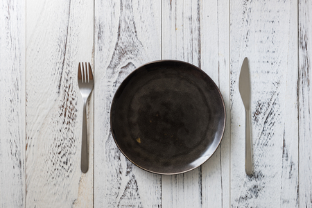 Black Round Plate with utensils on white wooden table background Stock fotó