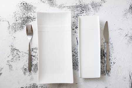 White rectangular Plates with fork and knife on white scraped wooden table background Stock fotó