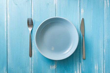 Blue Round Plate with utensils on blue wooden table background