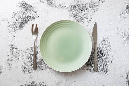 Green Round Plate with utensils on white scraped wooden table background Stock fotó