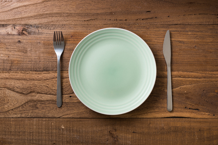 Green Round Plate with utensils on brown wooden table background