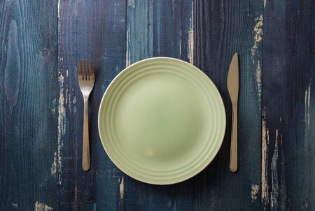 Green Round Plate with utensils on ocean blue wooden table background