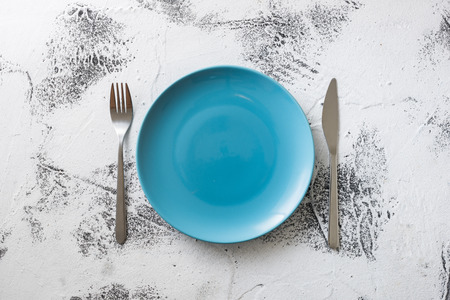 Blue Round Plate with utensils on white scraped wooden table background Stock fotó