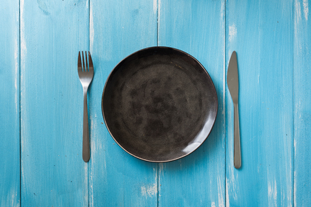 Black Round Plate with utensils on blue wooden table background Stock fotó
