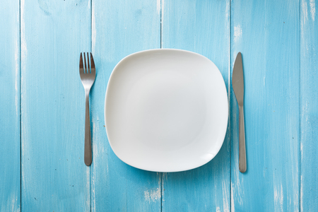 White Plate with utensils on blue wooden table background