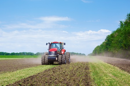 Modern tech red tractor plowing a green agricultural field in spring on the farm. Harvester sowing wheat. Mechanism