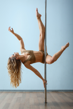 Young slim sexy blond woman in beige dress pole dancing against the background of the wall. 版權商用圖片