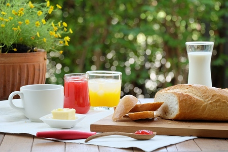 delightful: Delightful and Colorful Breakfast with bread, cheese, strawberry jam along wtih coffee, milk and orange juice in summer garden