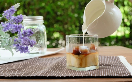 milk pouring: Relax with Ice Caffe Latte in the garden Milk pouring into a glass filled with espresso ice cube