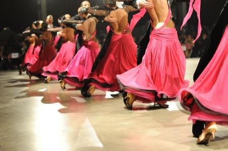 Ballroom Paare tanzen mit roten Pailletten tailsuits und Kleidern