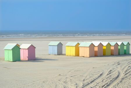 A sand beach with pastel colored wooden cabins photo
