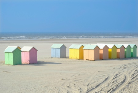 cabins: A sand beach with pastel colored wooden cabins