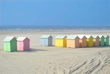 caba�a: Una playa de arena con caba�as de madera de colores pastel Foto de archivo