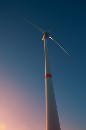 A wind turbine viewed from below in sunset light and blue sky photo