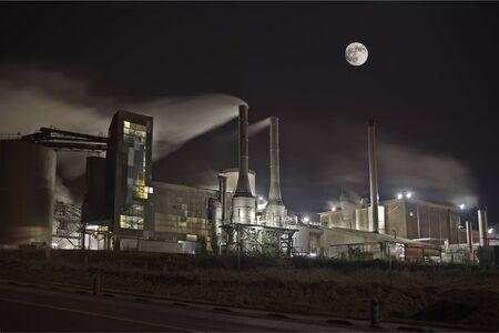 environmental issue: A polluting factory at night under full moon light