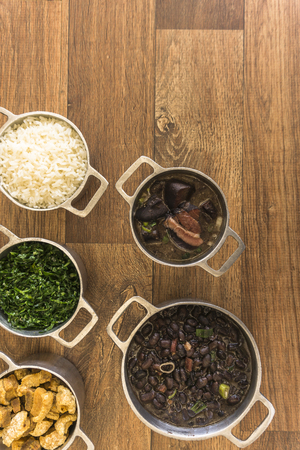 Dishes that are part of the traditional feijoada, typical Brazilian food.Black beans, cabbage, crackers, white rice, dried meat, paio Stock Photo