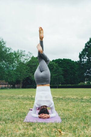 Young woman practicing yoga outdoors. Morning exercises.