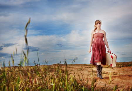 Smiling girl with suitcase in hand walking in the countryside